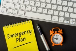 Notepad with Emergency or disaster plan on a workplace