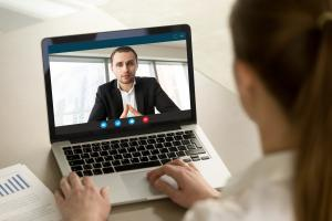 Businesswoman calling businessman online by video chat computer app, partners negotiating online on virtual meeting, employee reporting to boss running business remotely, close up rear view