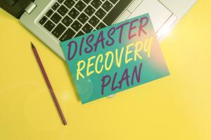 Conceptual hand writing showing Disaster Recovery Plan. Business photo showcasing having backup measures against dangerous situation Metallic laptop small paper sheet pencil colored background.