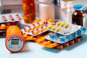 Pile of colorful medical pills in blisters and bottles on blue background. Drug and antibiotics prescription for treatment medication.
