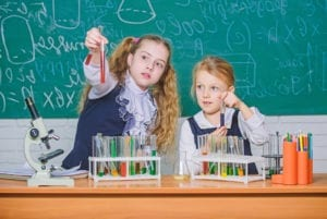 We love science. School children performing experiment in science classroom. Little girls scientists holding test tubes at lesson of natural science. Science laboratory for school and education